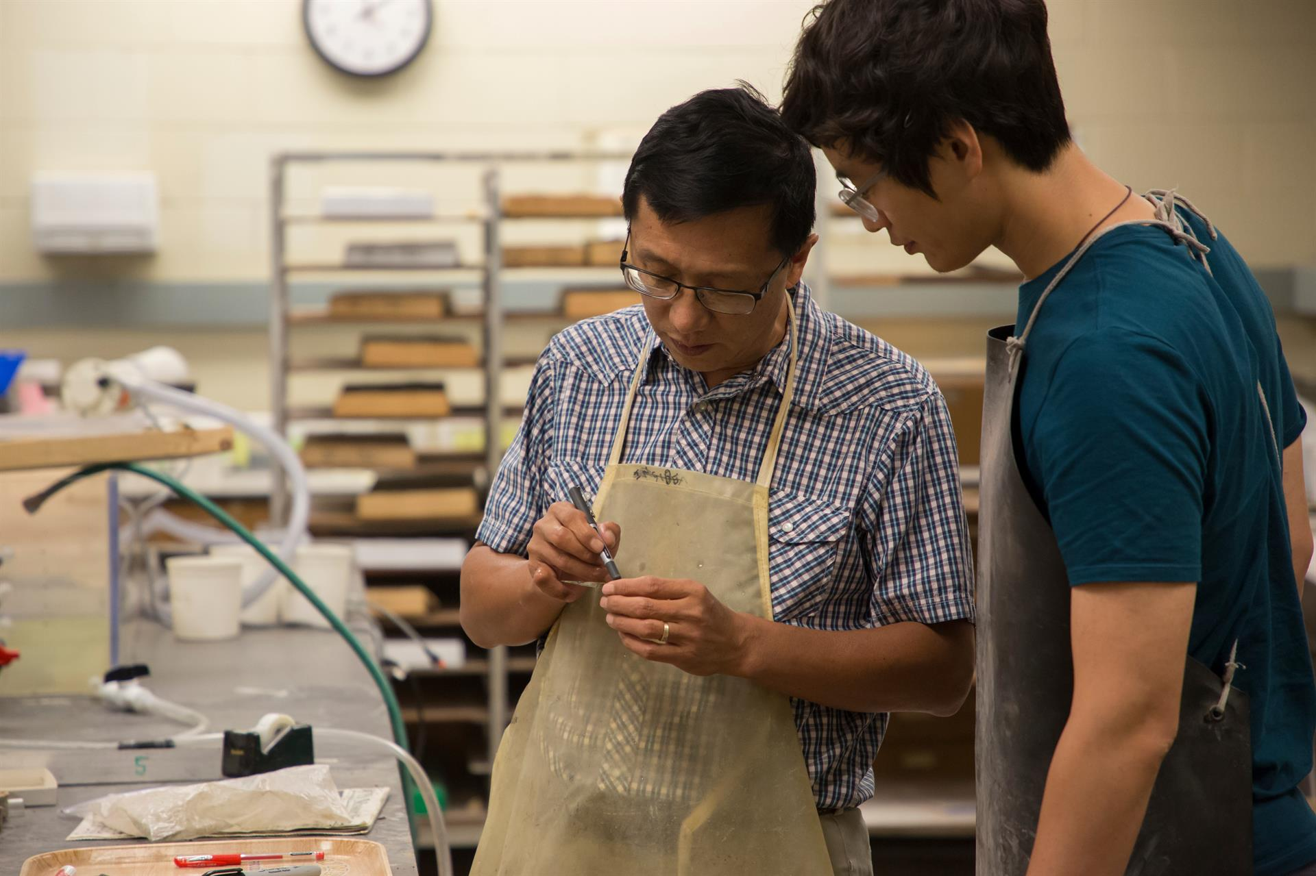 Dr. Wan Yang shows his research student Ziyue Ju how to properly label and cut rock samples for analysis.