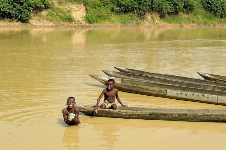 Two boys swim in the Tano River near Ghana's western border with Ivory Coast. Contamination from artisanal mining has rendered the river's water unfit for human consumption.